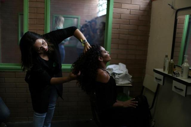 Chuyên gia trang điểm sửa lại tóc cho một thí sinh.