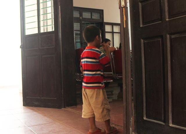 Một đứa trẻ dõi theo cha đang đứng trước vành móng ngựa từ cánh cửa cuối phòng xét xử.
