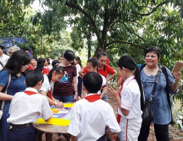 Các học sinh tiểu học ở TP Cao Lãnh thích thú trải nghiệm tham quan vườn xoài, vẽ tranh cổ động, giao tiếp tiếng Anh với du khách...