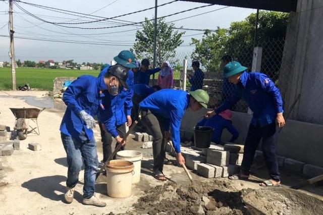 Các đoàn viên giúp người dân chỉnh trang lại vườn hộ, đường làng...