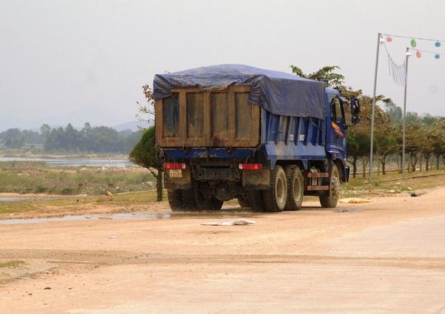 Các xe chở cát thấy sự xuất hiện của PV quay phim, chụp hình thì dừng lại để cho nước chảy bớt...