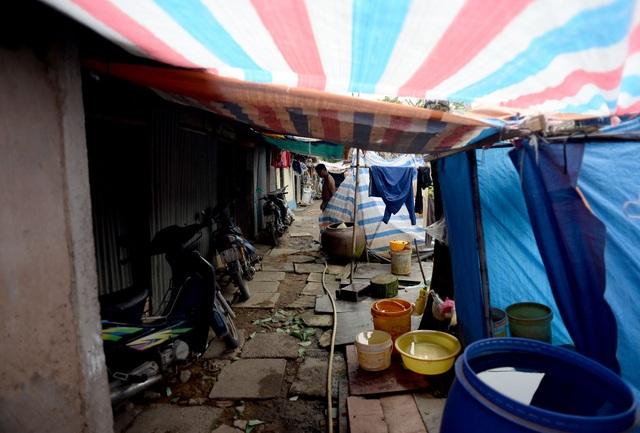 Để tiết kiệm không gian, xóm nhà lá chỉ có vài nhà vệ sinh. Dọc theo lối vào, 1 bên là phòng của các gia đình, một bên là nhà vệ sinh che tạm bằng tấm bạt.