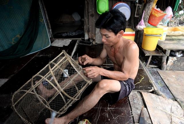 Gia đình anh Tuấn, quê Cà Mau đã sống hơn 10 năm ở xóm nhà lá này. Mấy hôm nay hết việc, anh Tuấn tranh thủ đan mấy ró đánh cá để kiếm thức ăn cho gia đình.