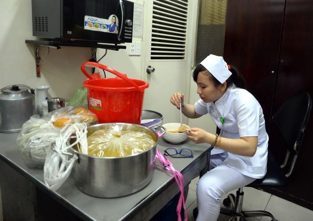 Nữ điều dưỡng Thiên Nga tranh thủ ăn vội chén mì trước khi bước vào công việc đêm 30 Tết.