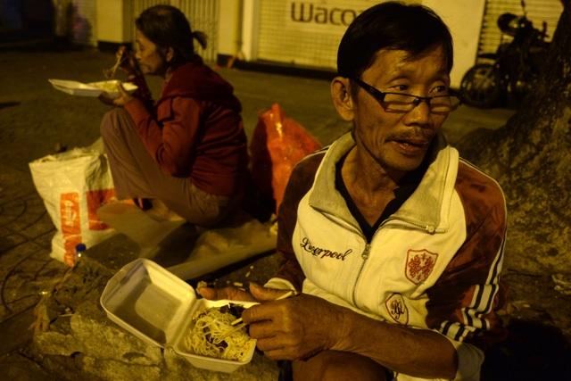 Khi ngày Tết là dịp để đoàn viên với gia đình, họ phải lang thang vỉa hè, ăn những phần ăn do người đi đường trao tặng. Vợ chồng bà Quỳnh Hoa (65 tuổi) đang ăn hộp mì xào do nhóm từ thiện phát rạng sáng mùng 1 Tết.