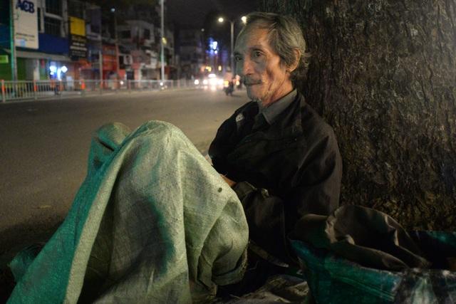 Ông Thái (70 tuổi) nép mình dưới gốc cây lớn đường 3 tháng 2, quận 10, dùng bao bố che kín thân để bớt lạnh.