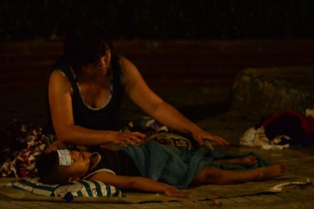 Cậu bé ốm sốt trong đêm giao thừa, được mẹ đắp mền trong lúc nằm ngủ trên vỉa hè.