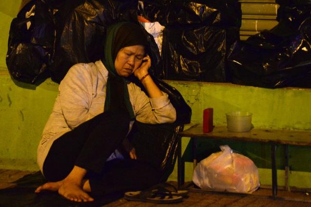 Bà Chín tựa mình vào vách tường nhà trên đường Lý Chính Thắng để ngủ.