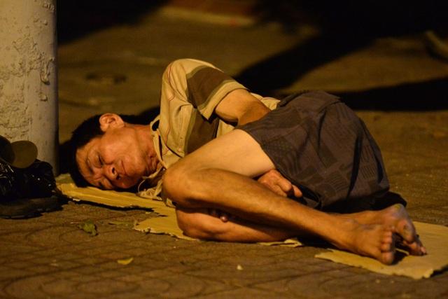 Người đàn ông nằm co ro trên tấm bìa giấy nơi vỉa hè, cô quạnh trong thời khắc nhà nhà sum vầy.