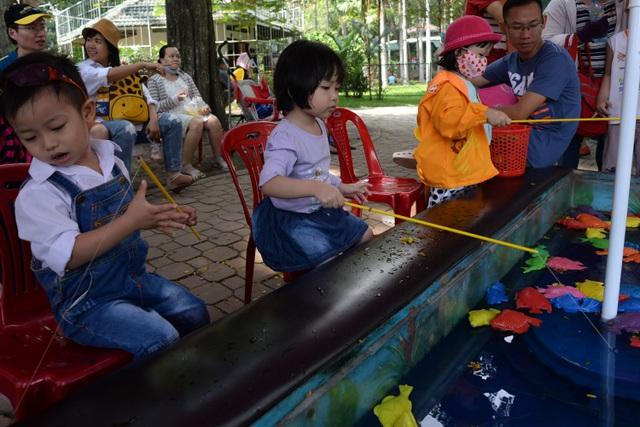 Các em nhỏ ngồi câu cá nhựa khi được bố mẹ dẫn đi chơi Xuân.