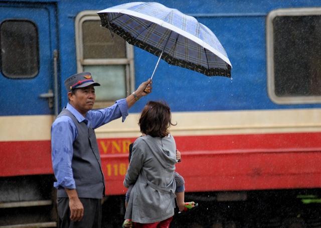 Chú Nguyễn Đức Thích (52 tuổi, đã có 32 năm công tác ở ga Quảng Ngãi) dùng dù che cho khách lên tàu khỏi ướt. Chú cho biết, thấy trời mưa lớn nên cầm dù ra phụ giúp mọi người lên tàu không bị ướt để bắt đầu 1 năm mới thật suôn sẻ.