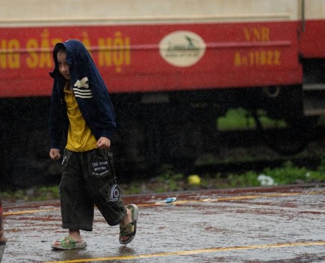 Cậu bé trùm tạm áo khoác lên đầu tránh bị ướt