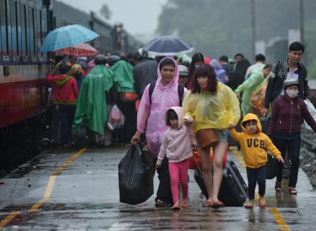 Người phụ nữ dẫn hai con đi trong mưa để lên tàu ở ga Quãng Ngãi