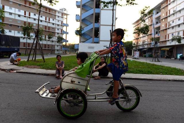 Trẻ em chơi trò chơi, người lớn ngồi hóng mát ở bãi cỏ bên trong khuôn viên khu dân cư.