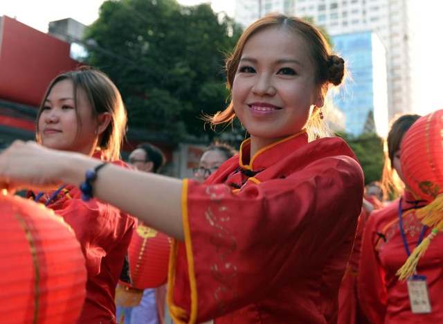 Những cô gái xinh xắn mang đèn lồng đi thành hàng dài trong đoàn diễu hành.