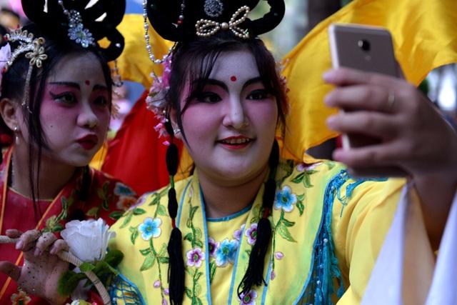 Hai cô gái đóng nàng tiên chụp hình kỷ niệm sau khi đoàn diễu hành dừng nghỉ.