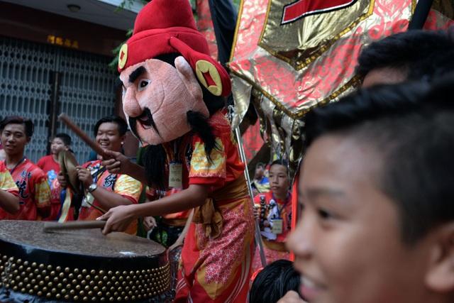 Một thành viên đoàn lân sư rồng đội mũ thần tài đánh trống khi diễu hành trên đường phố.