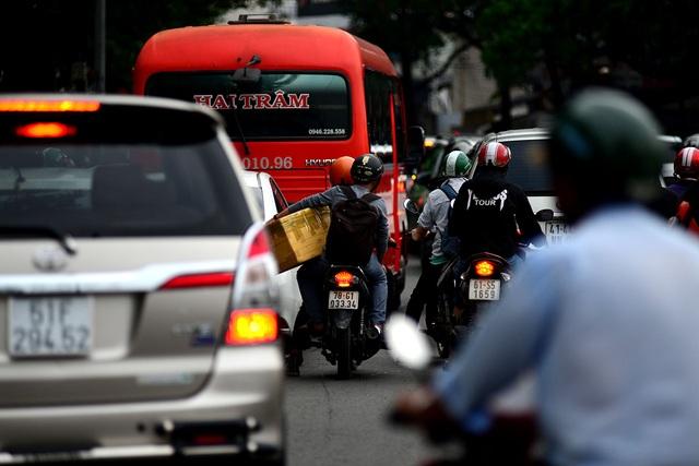 Nhiều người về quê bằng xe gắn máy, mang theo đồ đạc lỉnh kỉnh.