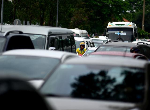 Người đàn ông đi xe gắn máy luồn lách vào đường đi của xe ô tô.