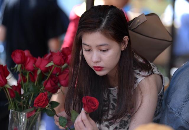 Ở cửa hàng hoa bên cạnh, một cô gái trẻ ngồi hơn 1h đồng hồ để chờ đến lượt nhận hoa.