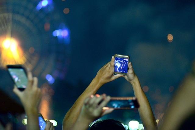 Người dân và du khách dùng điện thoại ghi lại cảnh pháo hoa được bắn lên.