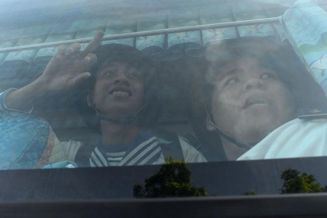 Thanh niên nhập ngũ vẫy tay qua cửa kính ô tô chào người thân.