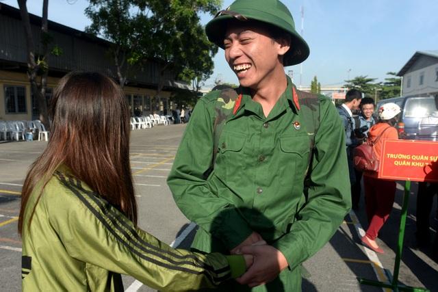 Tân binh nhập ngũ cười tươi, nắm tay tạm biệt người yêu để lên đường.