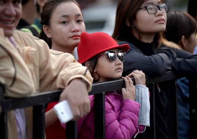 Nhiều em nhỏ đứng dọc phố đi bộ theo dõi buổi trình diễn.