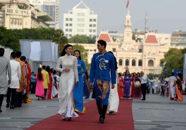Hàng nghìn người trong trang phục áo dài, bước trên thảm đỏ ở phố đi bộ.