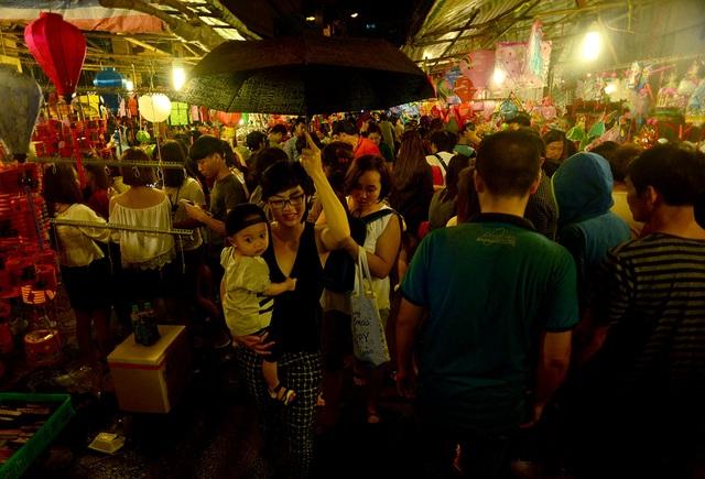 Dù trời mưa nặng hạt nhưng nhiều người vẫn che dù (ô) và mang áo mưa đi chơi.