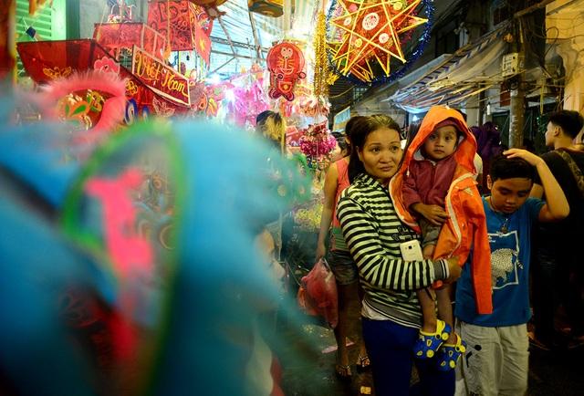 Những em nhỏ được ba mẹ dẫn đi chơi phố đèn lồng.