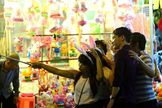 Các bạn trẻ chụp hình bên các gian hàng đèn lồng.