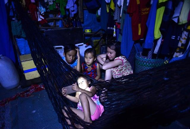 Vào buổi tối, những đứa trẻ thường tụ tập với nhau xem hoạt hình trên chiếc điện thoại được xem là hiện đại nhất xóm của anh Nghĩa.