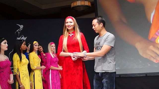 Đạo diễn Quang Tú hướng dẫn một người mẫu để tay sao cho thể hiện nét duyên dáng, thanh lịch của một cô gái Việt khi mặc áo dài.