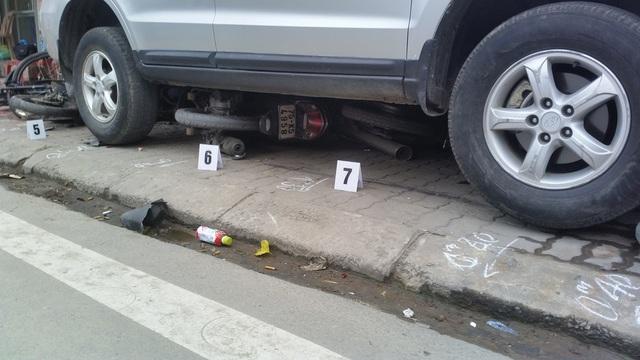 Giữa gầm xe ô tô là 2 chiếc xe máy nằm lọt phía dưới và bẹp dúm