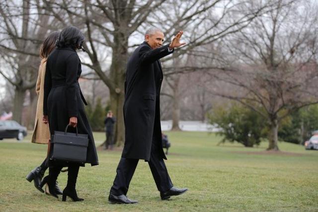 Tổng thống Obama vẫy chào khi cùng Đệ nhất phu nhân Michelle và con gái Malia rời Nhà Trắng để lên chuyến bay về Chicago. (Ảnh: Reuters)
