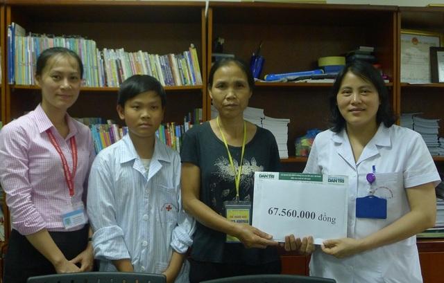 Ths.BS Nguyễn Thị Mai - Trưởng khoa Hemophilia, Viện Huyết học và Truyền máu Trung ương thay mặt trao quà bạn đọc Dân trí đến hai mẹ con chị Tú.