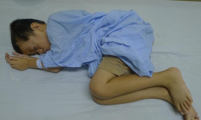 Cậu bé gần như không còn sức lực, nằm co quắp trên giường bệnh.