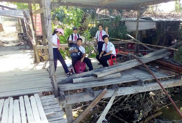 Các em học sinh ngồi đợi bạn ở một góc cầu gỗ đã được tháo dỡ do bão số 12