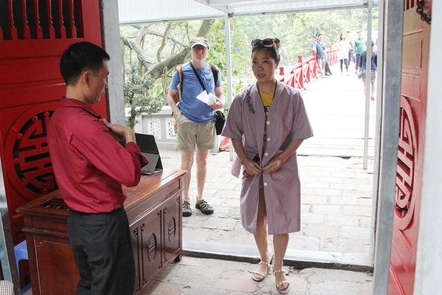 Nhân viên Ban quản lý nhắc nhở du khách cài khuy áo choàng khi vào đền Ngọc Sơn.