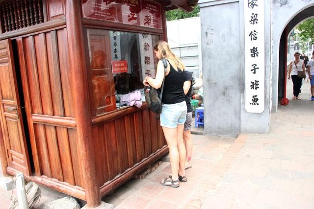 Nữ du khách nước ngoài làm thủ tục mượn áo choàng.