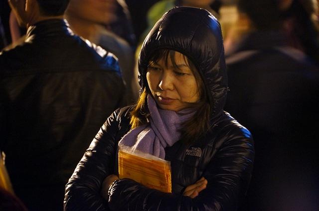 Chen chân sau một đêm dài, người phụ nữ này khá mệt mỏi khi xin được những cánh ấn cho gia đình và người thân.