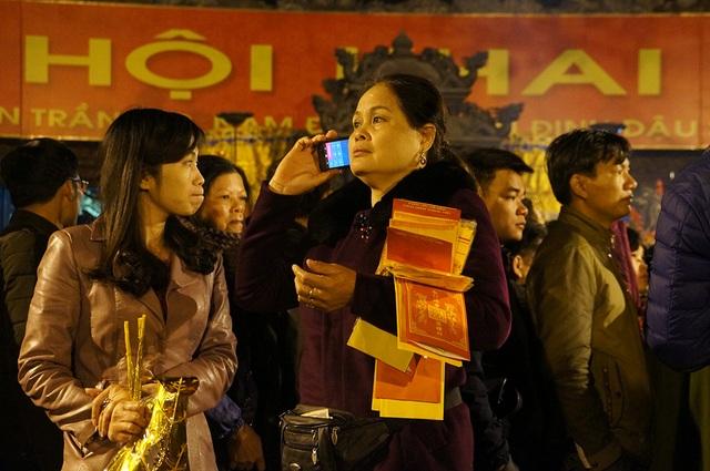 Một người phụ nữ trong tay ôm khá nhiều ấn Trạch đang gọi điện đợi người thân ở đền Thiên Trường xin ấn đền Trần.