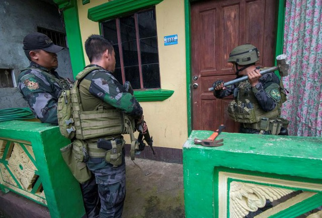 Một binh sĩ dùng búa phá cửa để lục soát một ngôi nhà trong thành phố.