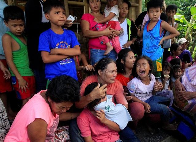 Người dân ở Pigcawayan ngồi chờ xe tới để đưa đi sơ tán sau cuộc tấn công của phiến quân (Ảnh: Reuters)