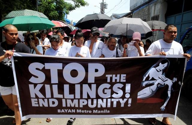 Những người thân của Leover Miranda mang theo biểu ngữ kêu gọi chấm dứt các vụ giết người tại Philippines trong lễ tang ngày 20/8. (Ảnh: Reuters)