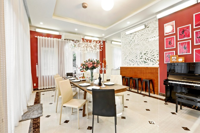 Kế đến là phòng bếp xa hoa như một căn bếp của gia đình hoàng gia. Một chiếc đàn piano được đặt cạnh bộ bàn ăn bằng gỗ, một chiếc đèn chùm sang trọng, một bình hoa, một cây nến.