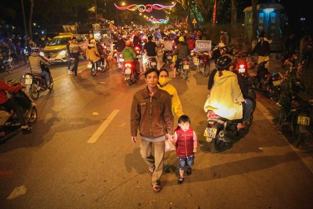 Cả gia đình người Huế cùng nhau đi chợ hoa đêm 30 Tết trong dòng người tấp nập