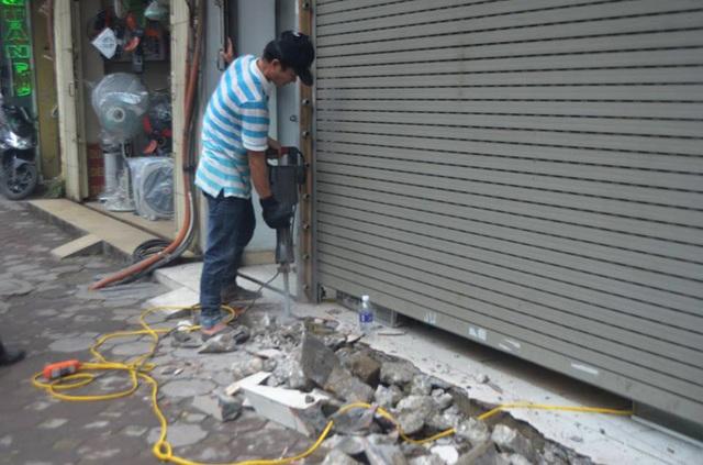 Máy khoan phá bê tông cầm tay được sử dụng để đập phá các bậc thềm, cầu dắt xe lấn chiếm vỉa hè của các hộ dân trên tuyến phố Nguyễn Lương Bằng.