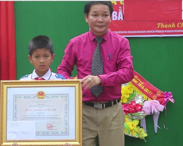 Ông Nguyễn Thanh Nhàn - PGĐ Sở Nội vụ - Trưởng ban thi đua khen thưởng tỉnh Nghệ An trao Huân chương dũng cảm cho em Tú.